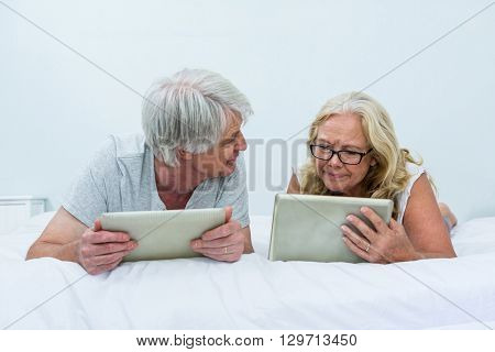 Senior couple talking while using digital tablets on bed at home