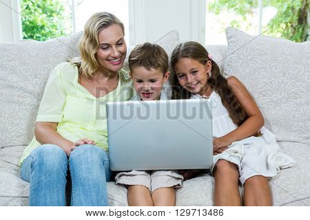 Happy mother by son and daughter using laptop on sofa at home