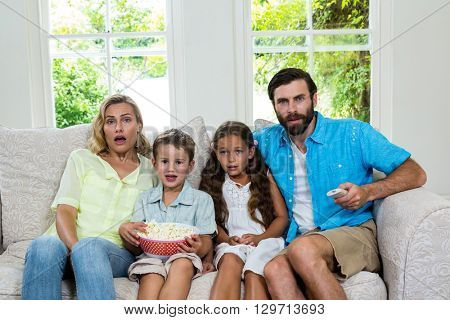 Portrait of surprised family laughing while watching tv at home