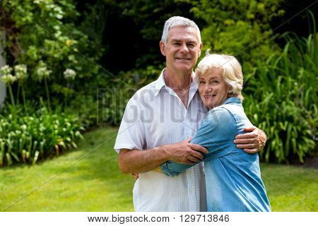 Portrait of happy senior couple embracing in back yard