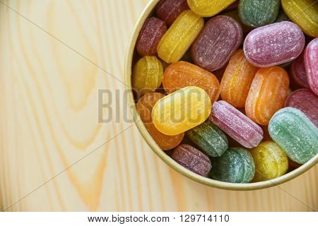 a lot of  sweet  colorful lollipops on wooden background
