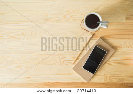 cup of coffee with a notebook on wooden background