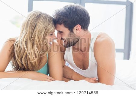 Young couple relaxing on bed face to face in the bedroom