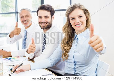 Business colleagues showing thumbs up in a meeting at office