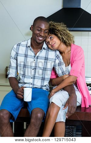 Young couple embracing and having coffee in kitchen