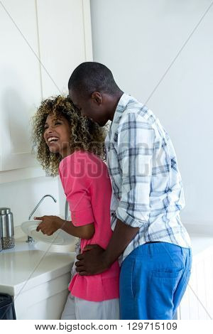 Man embracing woman while washing dishes in kitchen