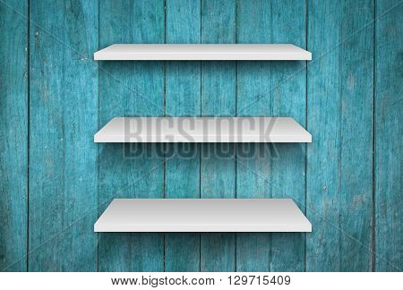 Three white shelves on blue wooden interior texture background, stock photo