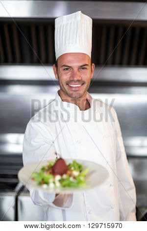 Portrait of smiling male chef holding plate while standing in commercial kitchen