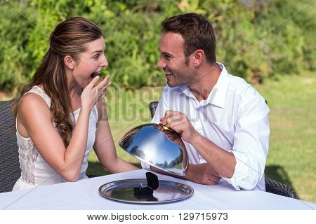 Husband holding cloche while proposing wife at park