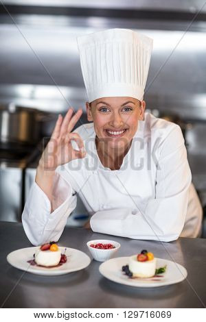 Portrait of smiling female chef showing ok sign in commercial kitchen
