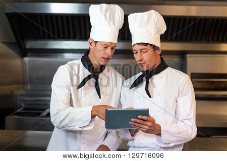 Male chefs holding clipboard while standing in commercial kitchen