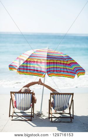 Cute mature couple doing high five on deckchairs on the beach
