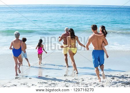 Cute multi generation family running in the sea on a sunny day