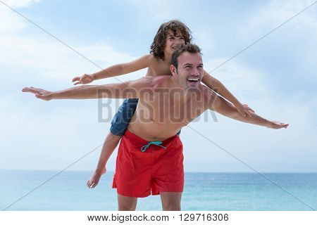 Man carrying son on back at sea shore against sky
