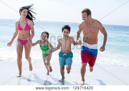Full length of family running while holding hands on sea shore at beach