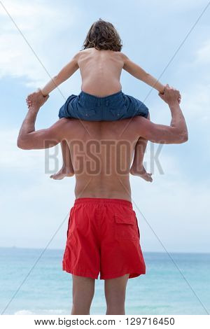 Rear view of man carrying son on shoulder at beach