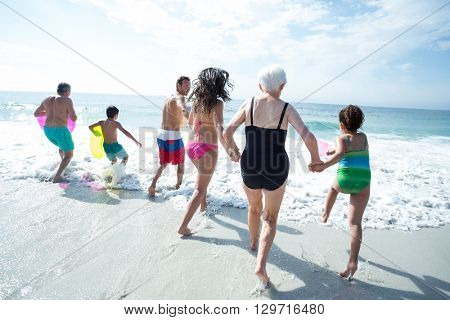 Rear view of multi-generation family enjoying at beach