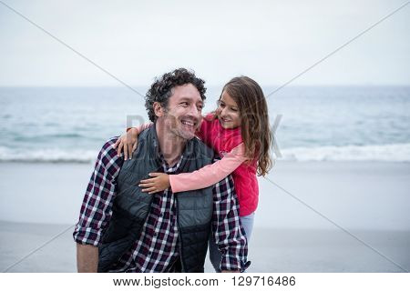Girl embracing smiling father while standing on sea shore at beach