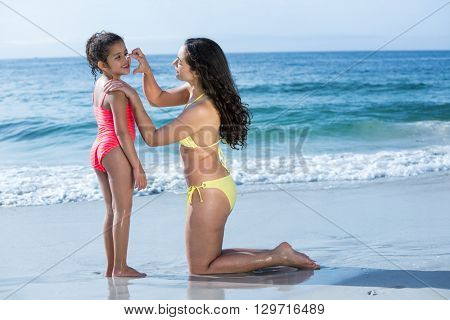 Mother applying cream to happy daughter at sea shore