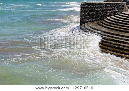 Waves crashing on concrete steps at the waterfront