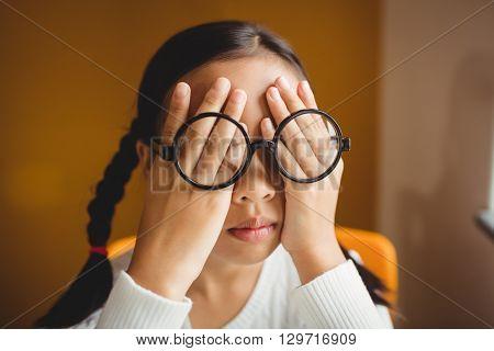 Schoolchild hiding her eyes at school