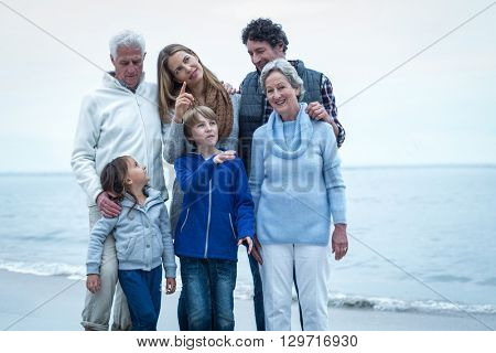 Happy family standing at beach against sky