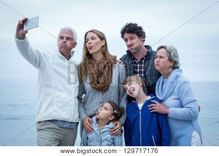 Multi-generation family making faces while taking selfie at sea shore