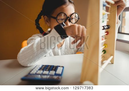 Schoolchild using a slide rule at school