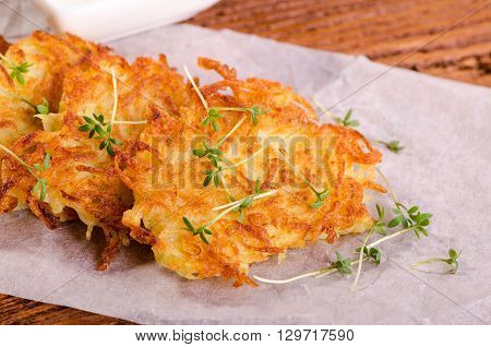 Potato pancakes with green sprouts on a sheet of parchment