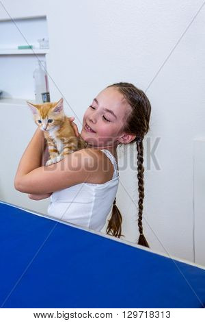 A little girl bringing a kitten at medical office
