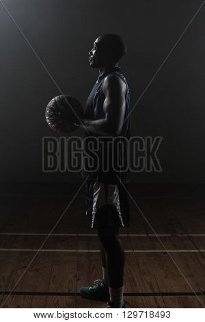 Side view of a basketball player holding a basketball against a dark background