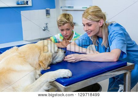 A woman vet and little boy playing with a dog on the operating table