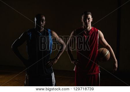 Portrait of basketball players posing with hands on hips on a gym