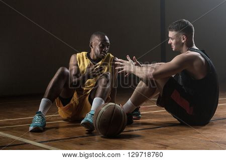 Basketball players sitting on floor talking together on gym