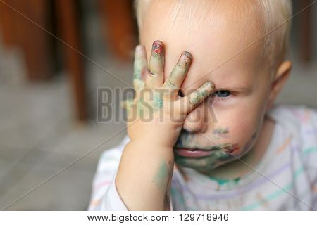 Cute Baby Girl Covering her Paint Covered Face with her Dirty Hands