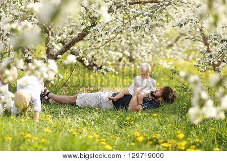 Father And Three Young Children Relaxing In Orchard On Spring Day