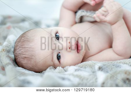Baby boy naked lying on back in white sunny bedroom on grey blanket on bed. Newborn child relaxing on bed after bath or shower. Nursery for children. Textile and bedding for kids. New born kid on grey towel.