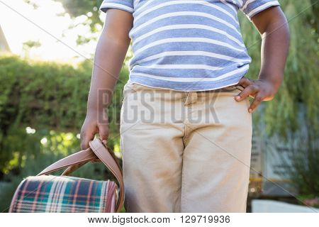Child with hand on hips holding a bag in the park