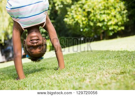 Portrait of a cute mixed-race girl smiling and doing a headstand on a park