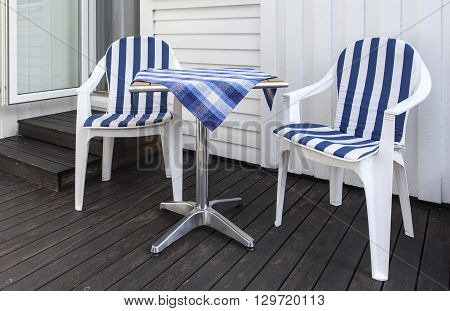 Patio furniture, blue and white on a balcony. Wooden wall in the background.
