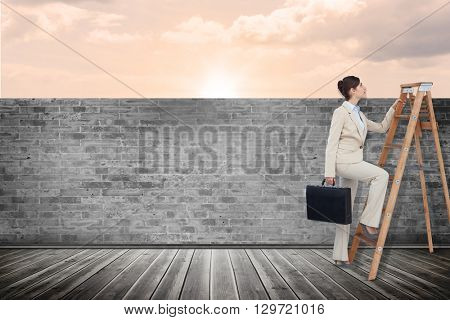 Businesswoman climbing career ladder with briefcase against a beautiful on a beach
