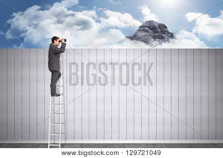 Businessman standing on ladder using binoculars against mountain peak through the clouds