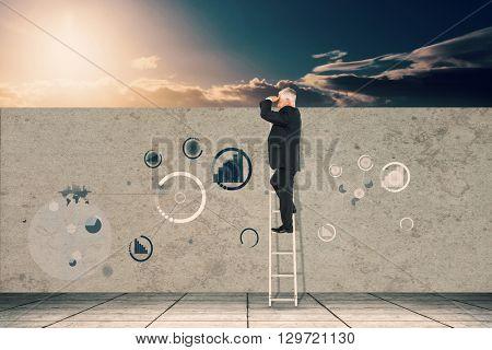 Mature businessman standing on ladder against a beautiful sunset on a beach