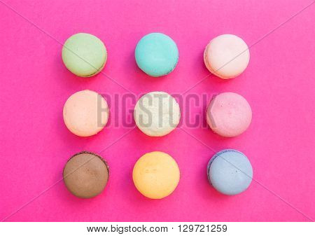 Sweet colorful French macaroon biscuits on bright fuchsia pink background, top view