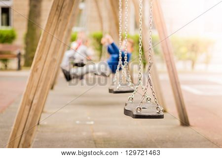 Empty chain swings in a playground. Blured background of swinging kids.