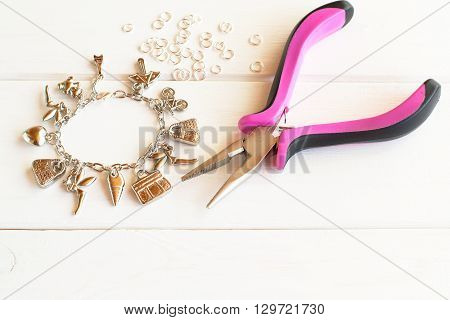 Pliers, bracelet, metal ring on a white wooden background. How to make yourself metal bracelet