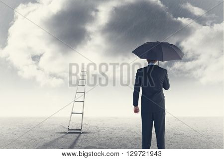 Rear view of businessman sheltering with umbrella against cloudy sky background