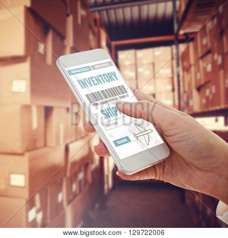 Cropped hand using smartphone against shelves with boxes in warehouse