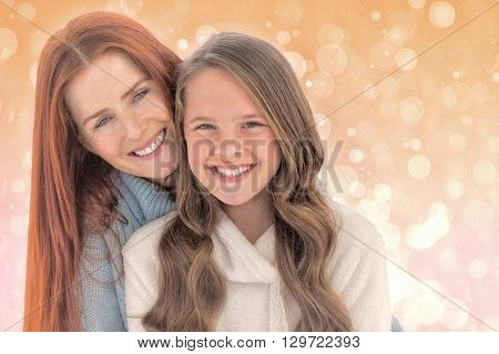 Portrait of happy mother with daughter against pink abstract light spot design