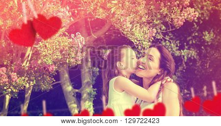 Composite image of mother and daughter holding each other in garden behind heart tinsel